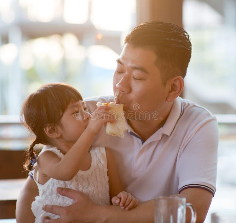 Fütterungsvatibrot des kleinen Mädchens stockfotografie