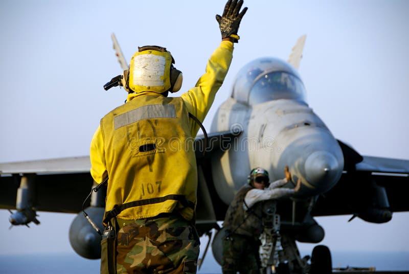 F-18 Hornet and Sailors. A Navy Sailor directs an F-18 Hornet fighter aircraft around the flight deck of an aircraft carrier stock photos