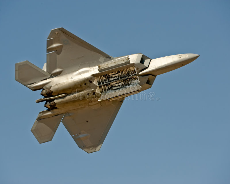F-22 Raptor aircraft in flight. Lockheed Martin/Boeing F-22 Raptor American military fighter in flight seen from underneath, blue sky background stock photography