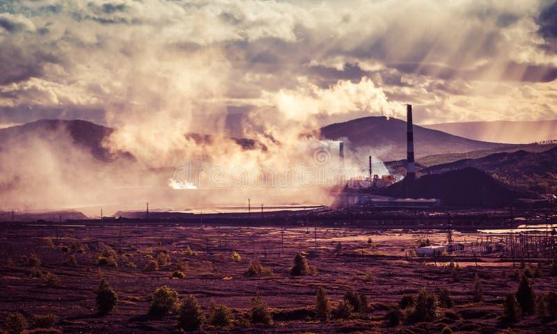 F?brica de la chimenea con humo negro sobre el cielo con la nube cuando tiempo de la puesta del sol, industria y concepto de la c foto de archivo