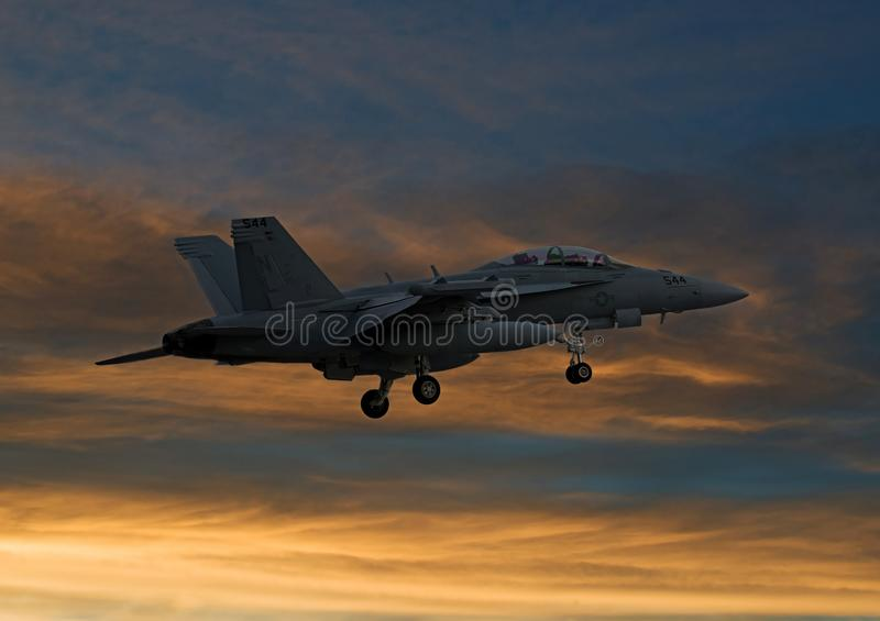 F/A-18 Hornet flying into the warm golden sunset sun stock photo
