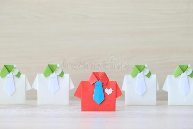 F?hrung und Teamwork-Konzept, rotes Hemd des Origamis mit Bindung und F?hrung unter kleinem gelbem Hemd auf wooder Hintergrund lizenzfreie stockbilder
