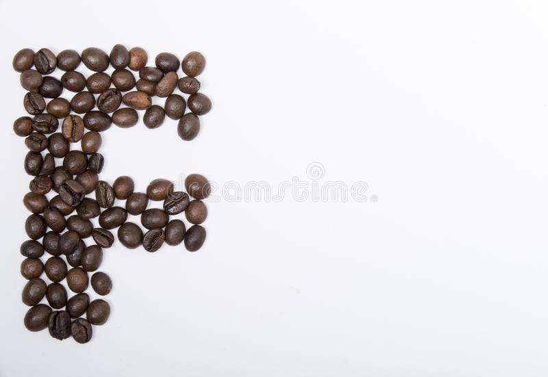 F - large letter of english alphabet. Made up of unmolished roasted coffee beans on a white background stock images