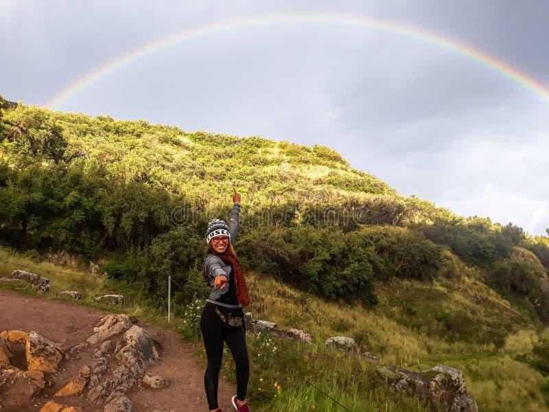 F?lj ditt dr?m- begrepp En kvinna som promenerar banan till berget och ser regnb?gen i himlen arkivfoton