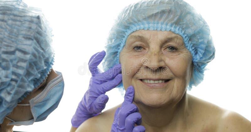 F?mea idosa de sorriso no chap?u protetor Cirurgi?o pl?stico que verifica a cara da mulher imagens de stock