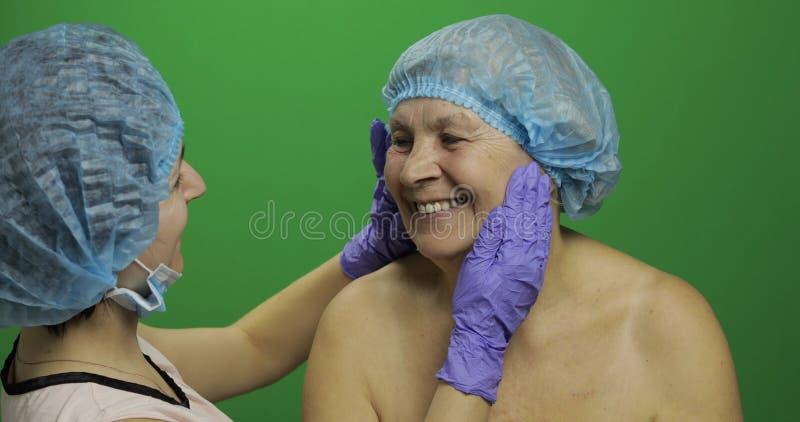 F?mea idosa de sorriso no chap?u protetor Cirurgi?o pl?stico que verifica a cara da mulher foto de stock royalty free