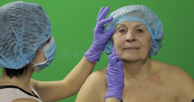 F?mea idosa de sorriso no chap?u protetor Cirurgi?o pl?stico que verifica a cara da mulher foto de stock