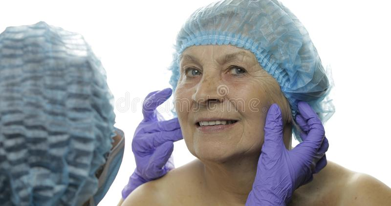 F?mea idosa de sorriso no chap?u protetor Cirurgi?o pl?stico que verifica a cara da mulher fotos de stock
