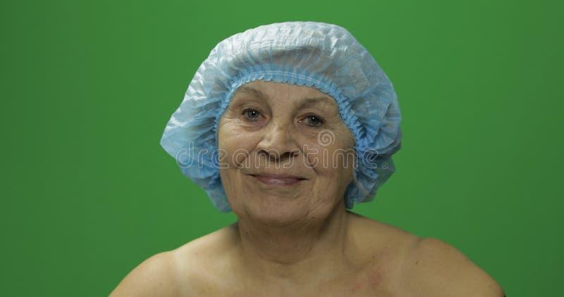 F?mea idosa de sorriso no chap?u protetor que olha ? c?mera Cirurgia pl?stica imagem de stock