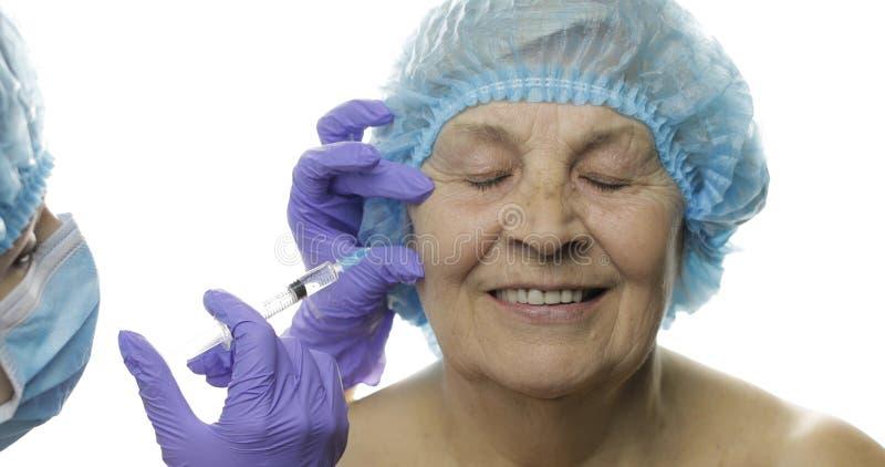 F?mea idosa no chap?u protetor Doutor que faz inje??es faciais para o paciente foto de stock