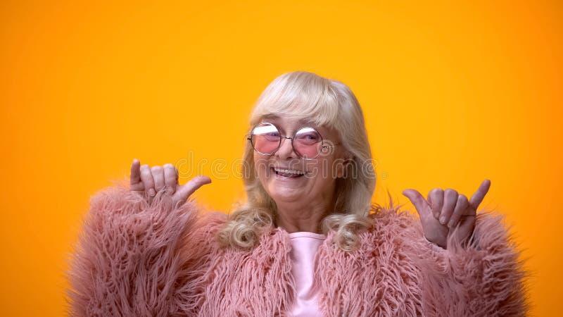 F?mea idosa positiva engra?ada no revestimento cor-de-rosa que faz o gesto do balancim, tendo o divertimento fotografia de stock