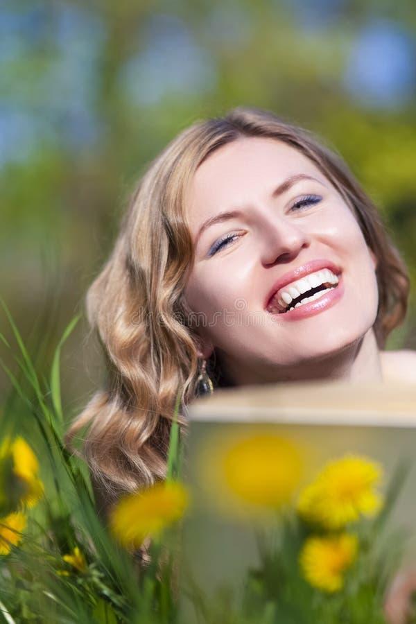 F?mea loura caucasiano de sorriso feliz com ar livre da leitura do livro na grama fotografia de stock