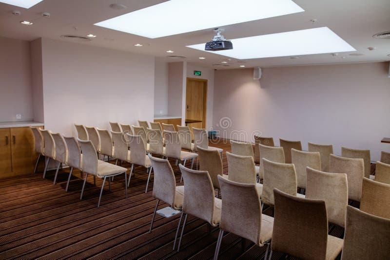 F molte sedie comode beige dell'ufficio nella sala con le pareti del luminoso lillà fotografia stock