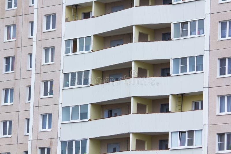 F?nsterbakgrund av h?g m?ng--v?ning en bostads- byggnad m?nga f?nster arkivbilder