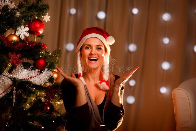 för ståendetree för jul lycklig near kvinna arkivbilder