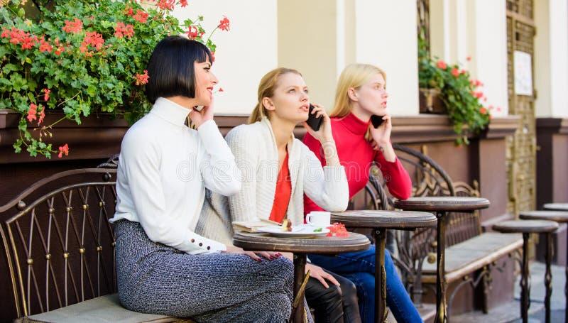 F?r Digital f?r m?ngfaldfolkanslutning bl?ddra apparater Social nätverkande på kafét tre flickor i kafét som talar på telefonen arkivfoton