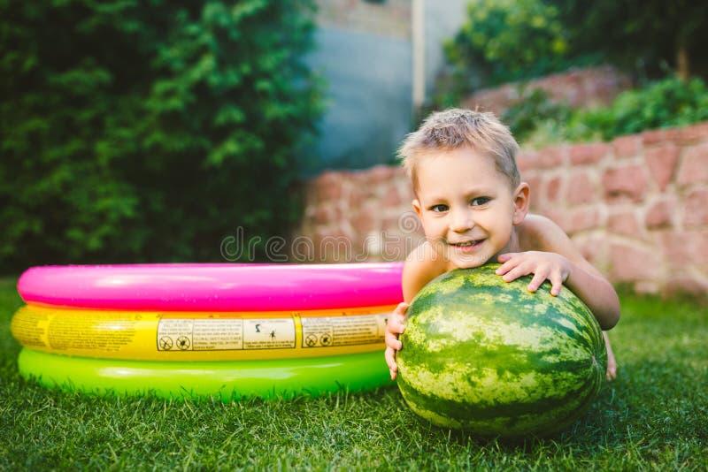 F?r gullig Caucasian vit europeisk sittande krama lopppojke f?r litet barn rymma den enorma vattenmelon och le p? bakgrund av gr? arkivbild
