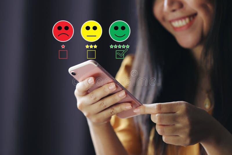 F?r handinnehav f?r ung kvinna smartphone och s?tta kontrollfl?cken med den smiley framsidamark?ren och den gr?na mark?ren p? fem arkivfoto