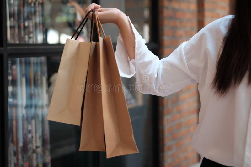 F?r innehavf?rs?ljning f?r ung kvinna p?sar f?r shopping arkivbild