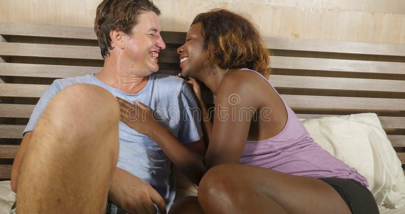 F?r?lskad kel f?r blandade etnicitetpar tillsammans hemma i s?ng med den h?rliga sk?mtsamma svarta den afrikansk amerikankvinnan  arkivfoton