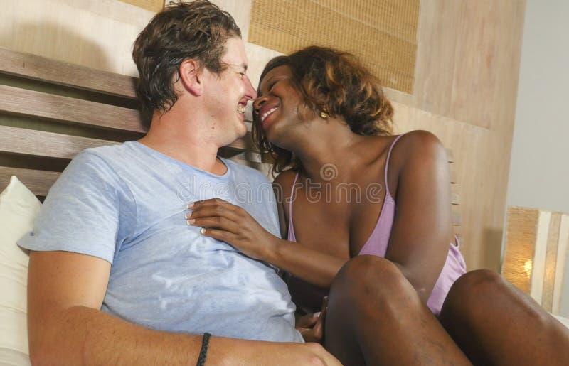 F?r?lskad kel f?r blandade etnicitetpar tillsammans hemma i s?ng med den h?rliga sk?mtsamma svarta den afrikansk amerikankvinnan  arkivbilder