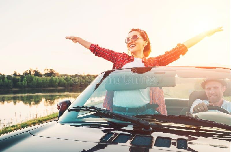 F?r?lskade lyckliga par passerar cabrioletbilen i solnedg?ngtid arkivfoto