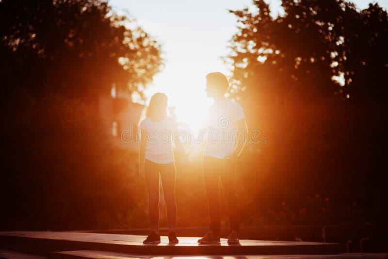 F?r?lskade tyckande om ?gonblick f?r par under solnedg?ng royaltyfri foto