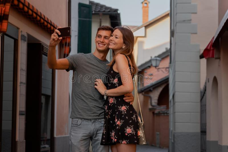 F?r?lskade unga par ta en selfie under shopping i en gr?nd i ascona royaltyfri foto