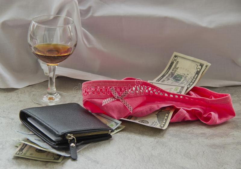F?r?lskelse f?r pengar ?r prostitution Ett skrynkligt ark, ett exponeringsglas av vin och pengar i hennes underkl?der ?r k?nsbest arkivfoton