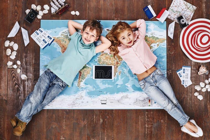 f r Mim e n d S Crianças que encontram-se no mapa do mundo perto dos artigos e do iPad do curso imagens de stock