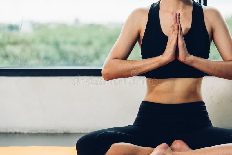 F?r yogal?nelyft f?r h?rlig kvinna sittande hand f?r ?vningsgenomk?rare p? mattt fotografering för bildbyråer
