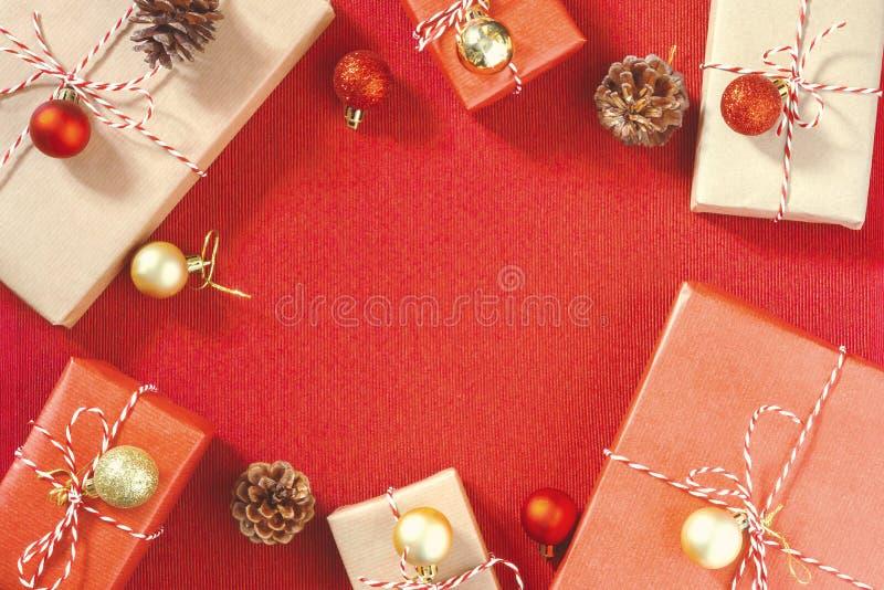 F?rbereda sig f?r ferien - inpackning av jul- eller julg?vor i r?tt och beige inpackningspapper royaltyfri fotografi