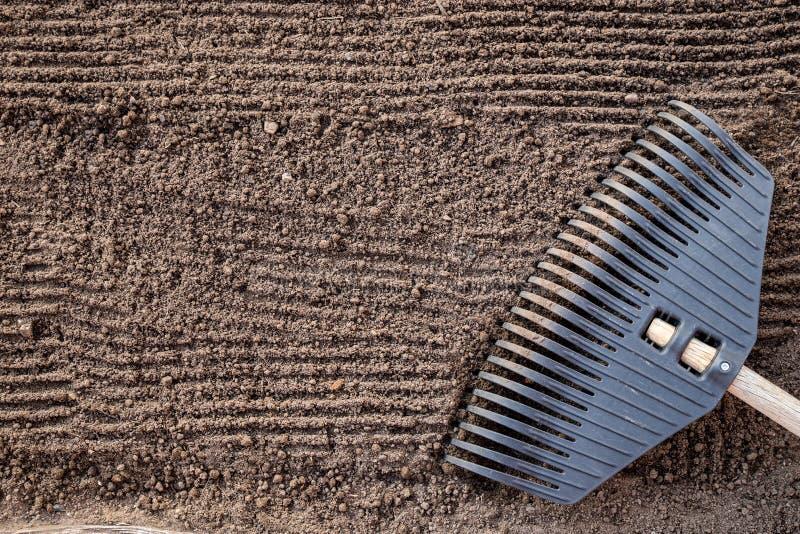 F?rberedelse av land, innan att plantera Texturen av jorden med horisontalspår från krattar, ordnar till för att plantera royaltyfri fotografi