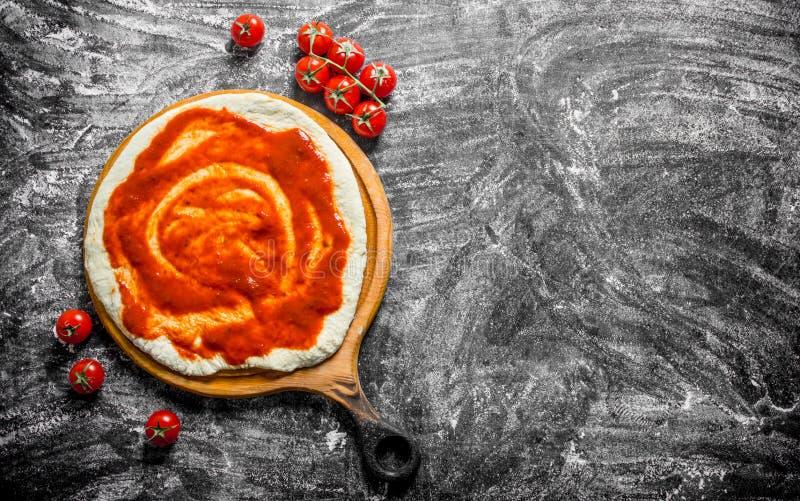 F?rberedelsepizza Deg på en skärbräda med körsbärsröda tomater arkivbild