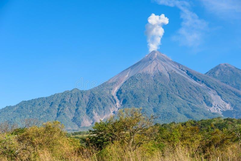 F?rbluffa vulkan El Fuego under ett utbrott p? v?nstersidan och den Acatenango vulkan p? r?tten, sikt fr?n Antigua, Guatemala royaltyfria foton