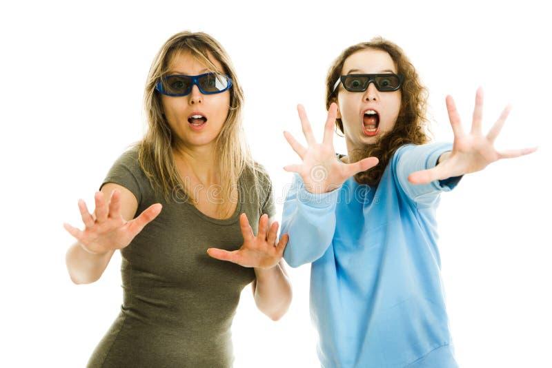 F?rbluffad kvinna och flicka i bion som b?r exponeringsglas som 3D erfar effekt f?r bio 5D - skr?md h?llande ?gonen p? kapacitet  royaltyfri bild