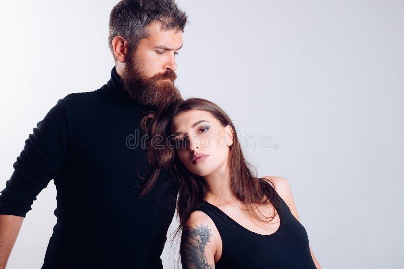 f?rbunden f?r?lskelse brutal sk?ggig man och kvinna med tatueringen Fris?r och frisersalong Tatueringsalong manlig sk?ggomsorg royaltyfri foto
