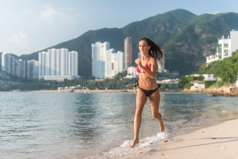 F?rdig b?rande bikinispring f?r kvinnlig idrottsman nen p? stranden med solen som in camera skiner, och hotellsemesterortkullar i royaltyfri foto