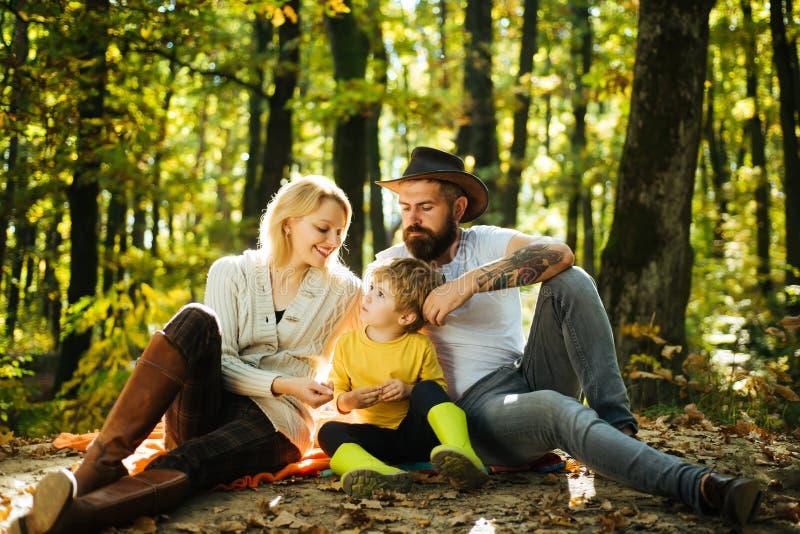 F?renat med naturen Familjdagbegrepp Lycklig familj med ungepojken som kopplar av, medan fotvandra i skogmoderfader och arkivbild