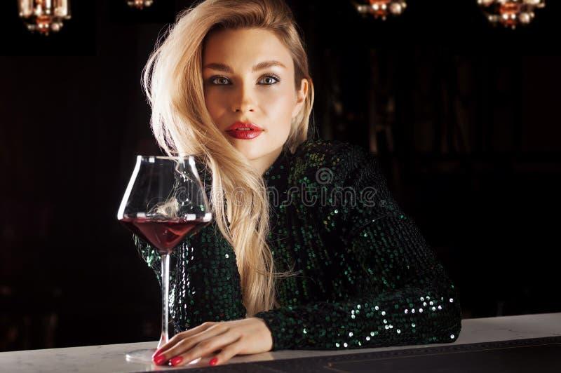 F?rf?risk blondin i en gr?n aftonkl?nning som poserar med ett exponeringsglas av r?tt vin arkivfoto