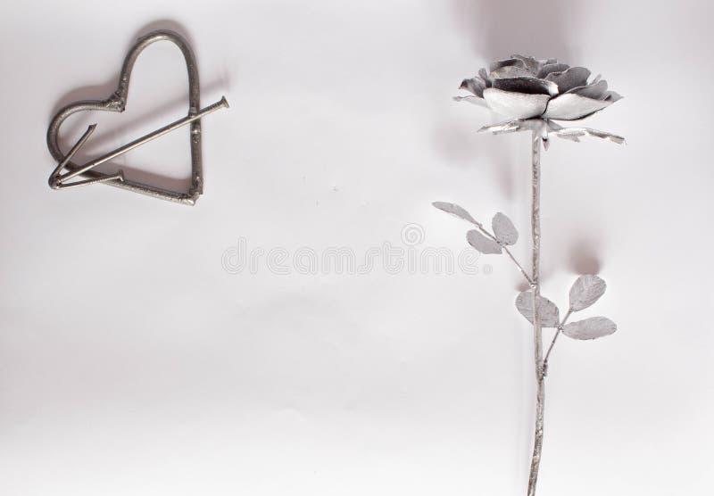 F?rfalskad handgjord metall f?r hj?rta spikar p? en vit bakgrund Falsk ros och hj?rta L?genheten l?gger, det minsta begreppet f?r royaltyfri fotografi