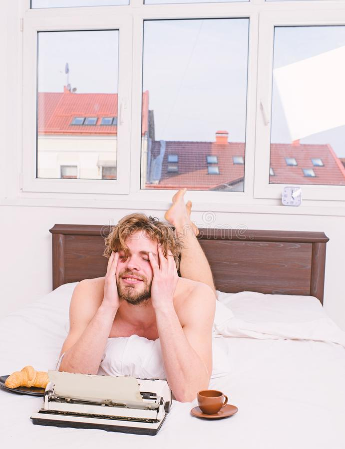 F?rfattaredrinkkaffe har frukosten i s?ng Brist av inspiration eller id?n Kreativitetkris Tr?tt desperat f?rfattare f?r f?rfattar royaltyfri fotografi