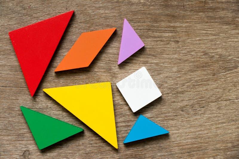 F?rgrik tangrampusselv?ntan att framkalla form p? tr?bakgrund arkivbilder