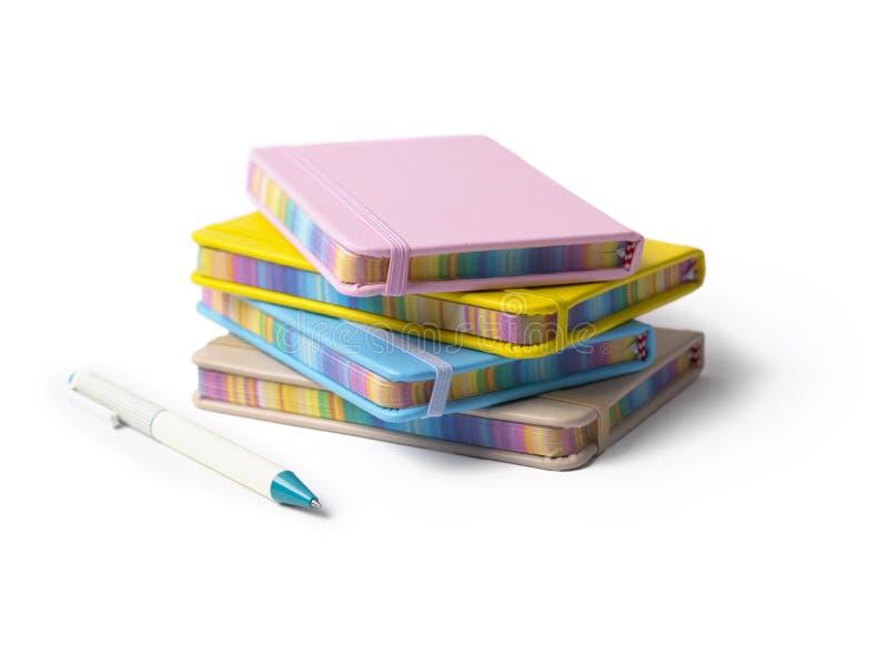 F?rgrika anteckningsb?cker med pennan som isoleras p? vit bakgrund tillbaka begreppsskola till royaltyfri bild
