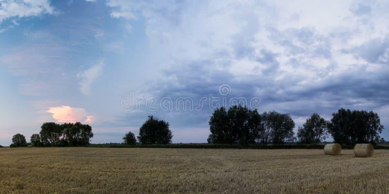 F?rgrika moln ?ver f?lt fotografering för bildbyråer