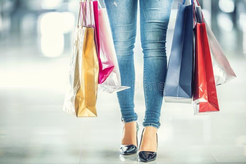 F?rgrika shoppa p?sar i h?nderna av en shopparekvinna och hennes benjeans och skor royaltyfri foto