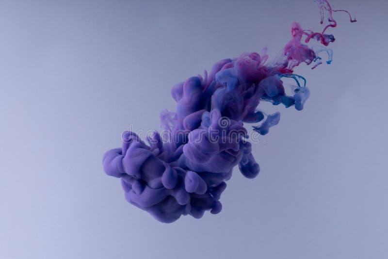 F?rgrikt f?rgpulver som virvlar runt i vatten Moln av silkeslent färgpulver på vit bakgrund royaltyfri foto
