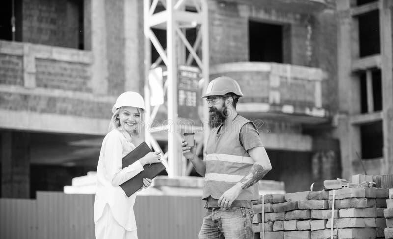 F?rh?llanden mellan konstruktionsklienter och deltagarebyggnadsbransch Kvinnatekniker och brutal byggm?stare fotografering för bildbyråer