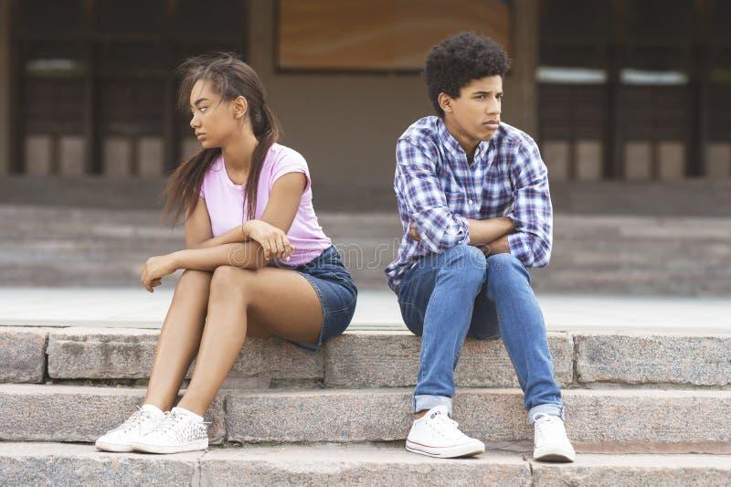F?rh?llandeproblem Svarta tonårs- par som är separata efter argument royaltyfria foton