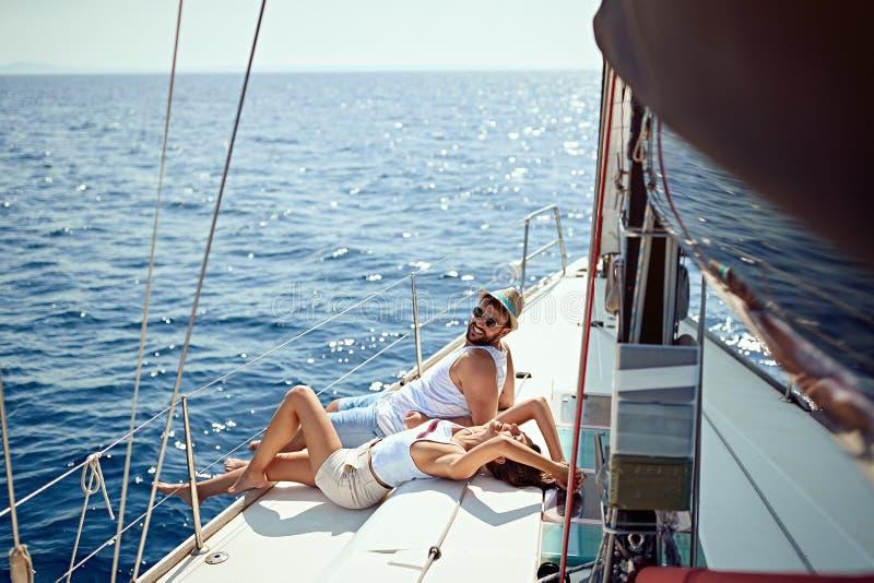 F?rias rom?nticas e curso luxuoso Pares de amor novos que sentam-se na plataforma do iate Navegando o mar fotografia de stock